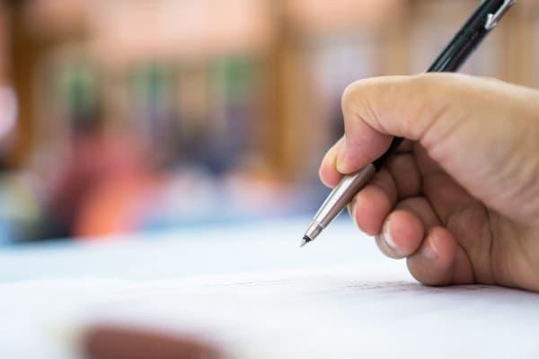 Assistência Técnica em Perícias Grafotécnicas: pessoa assinando um documento.