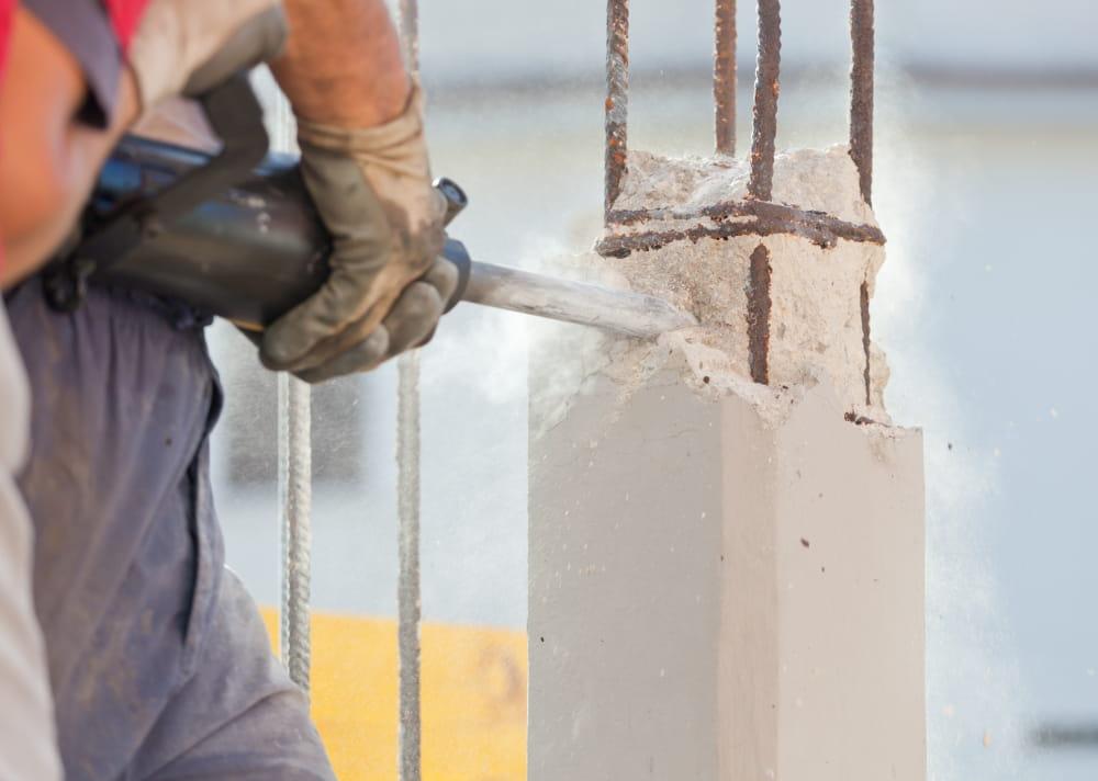 Laudo de Insalubridade: trabalhador com uma britadeira quebrando um pilar.